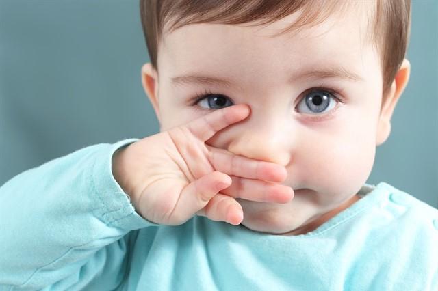 маленький ребенок закрывает лицо ручкой
